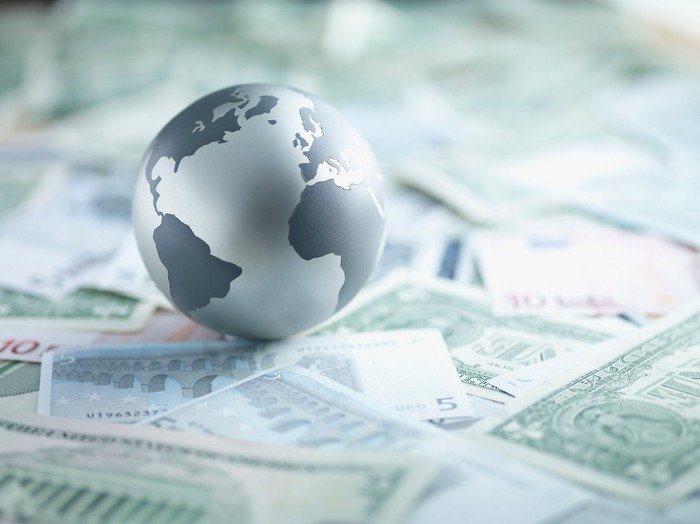 A globe sitting on top several foreign currencies.