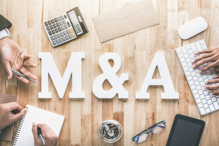 """A top-down view of a table with """"M&A"""" in big, block letters and hands writing in notebooks and typing on keyboards"""