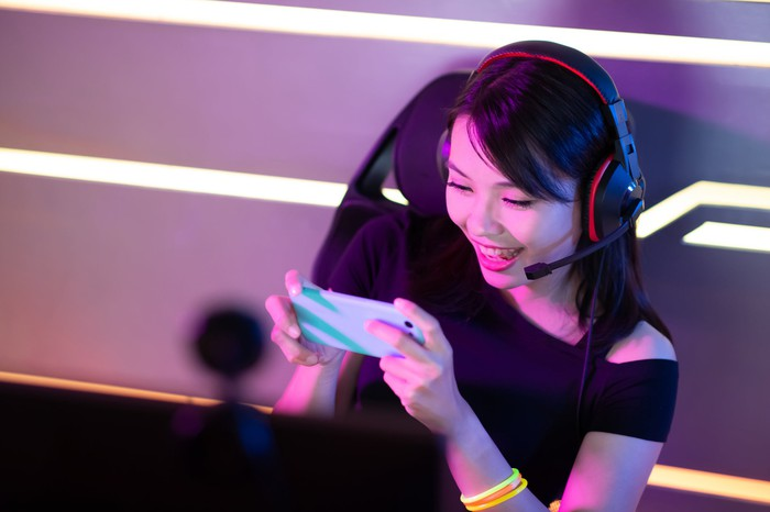 Gamer wearing a headset livestreaming on a smartphone