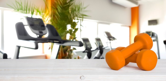 Two yellow dumbells with exercise machines in the background.