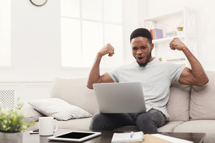 Man on couch cheering with arms raised and happy his laptop is working