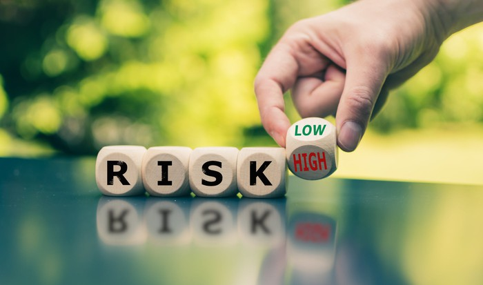 A series of wooden cubes form the word RISK. A hand is lifting the final cube, holding it between the LOW and HIGH sides.