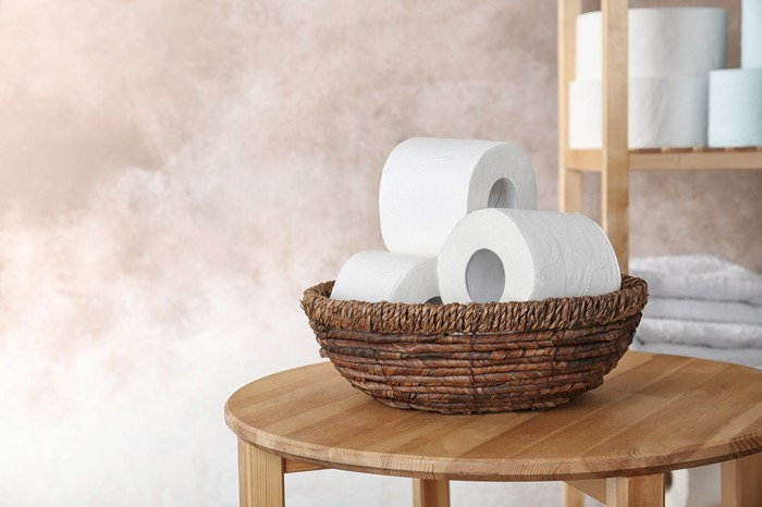Straw bowl on wood table, filled with several toilet paper rolls