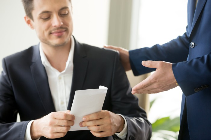 Man in suit smiling and holding document while standing man in suit pats him on the back and extends his hand