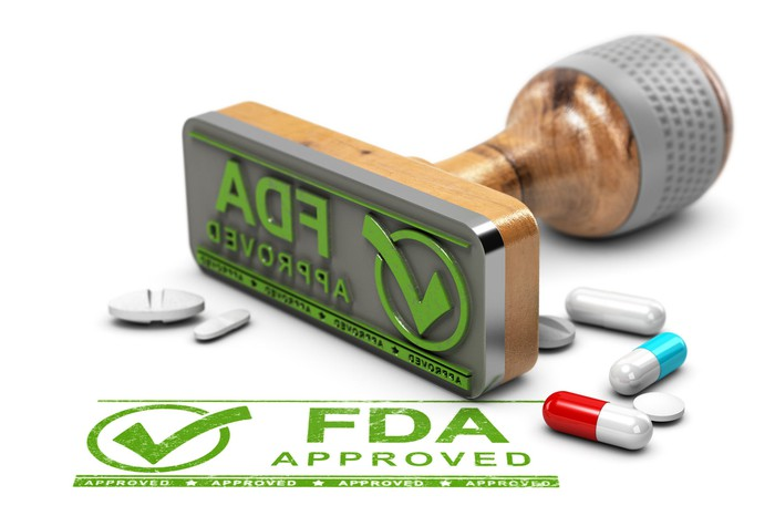 "A stamp marked ""FDA Approved"" is shown next to a few pills."
