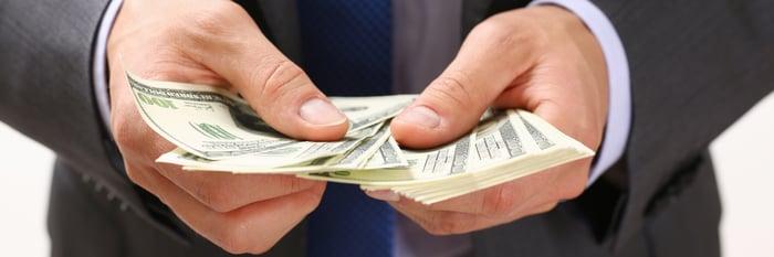banker handing out cash representing loan