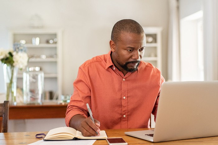 Man at laptop taking notes in notebook