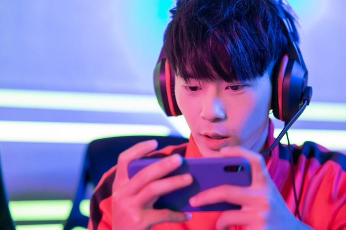 A boy wearing headphones holding a smart phone playing a video game.