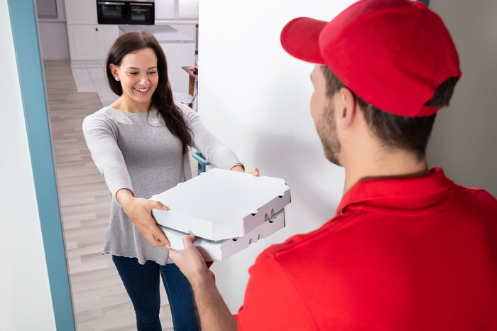 Man in a red shirt and baseball cap delivering two boxes of pizza to a brown-haired young woman wearing gray.