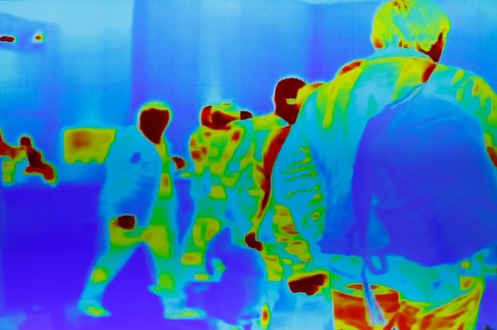 Crowd of people viewed as thermal images.
