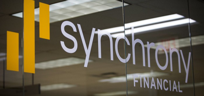 Synchrony Financial logo on glass wall in office.