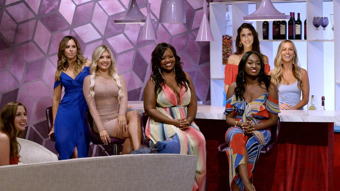 A group of seven fashionably dressed women on the set of a reality show.