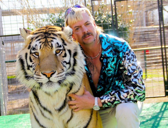 A man in a brightly colored shirt hugging a tiger.