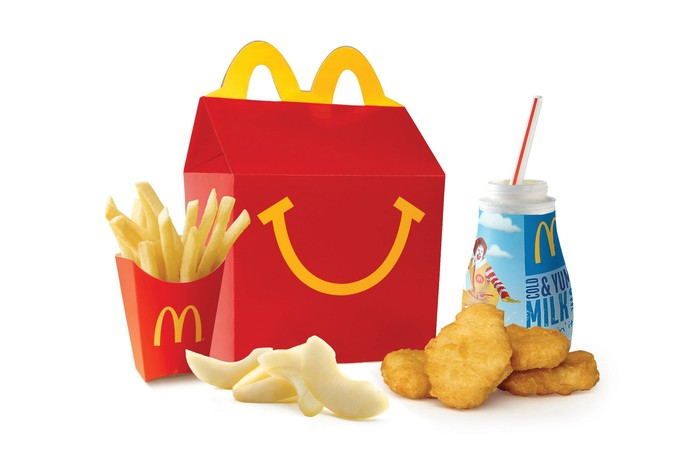 A kids Happy Meal, with fries, apple slices, chicken nuggets, and a cup of milk.