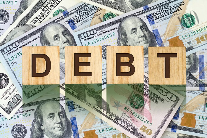 Wooden cubes spelling the word 'debt' on top of $100 bills.