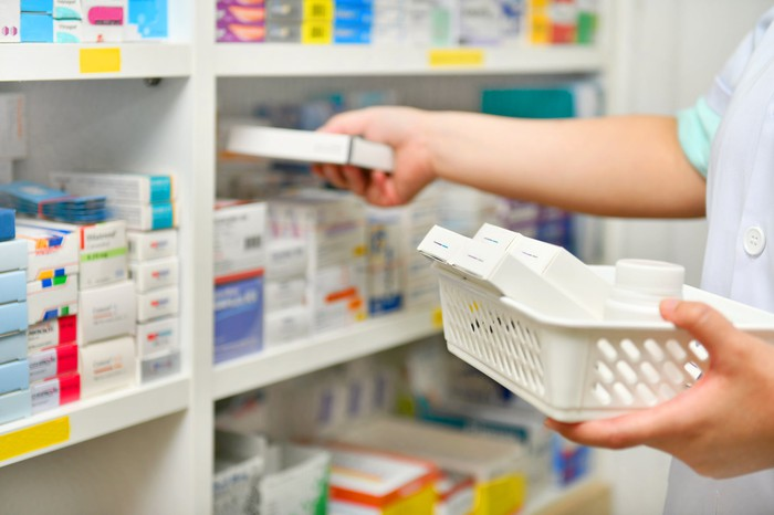 pharmacy worker stocking shelves