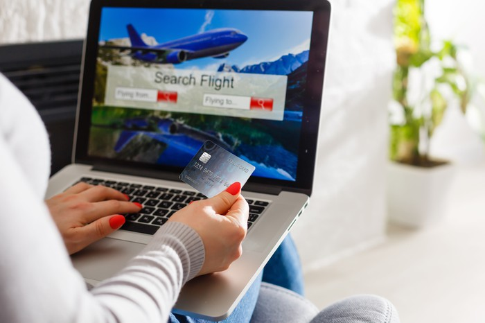 A woman booking a flight on her laptop computer while sitting on the couch.