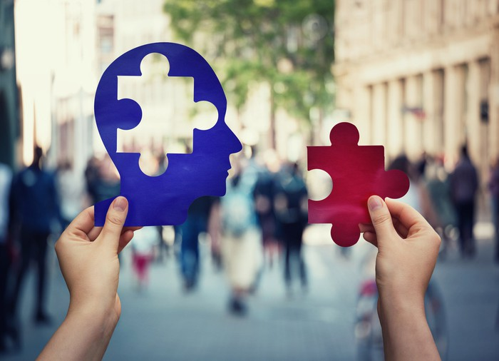 Hand holding a blue figure of a human head with a jigsaw cutout with another hand holding a red jigsaw puzzle piece that fits into the opening