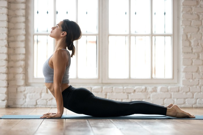 A woman holds a yoga pose in front of a bright window.