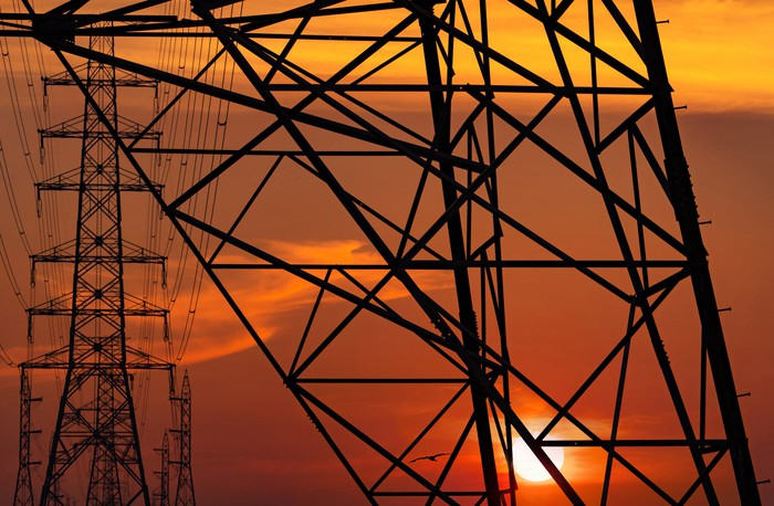 High voltage electrical poles and wires at sunset.