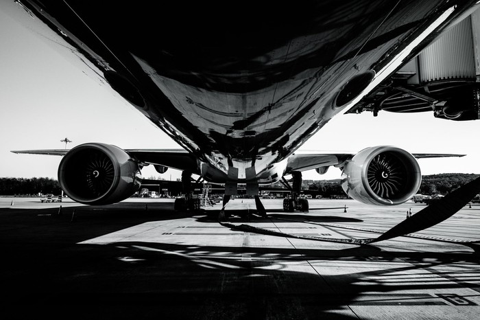 Black and white picture of an airplane from underneath while on the ground.