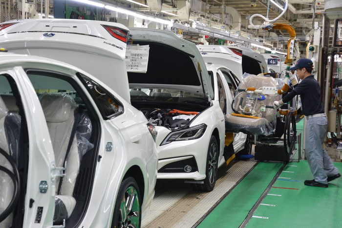 A worker attends to vehicles on a production line at Toyota's Motomachi plant in Toyota City, Japan.