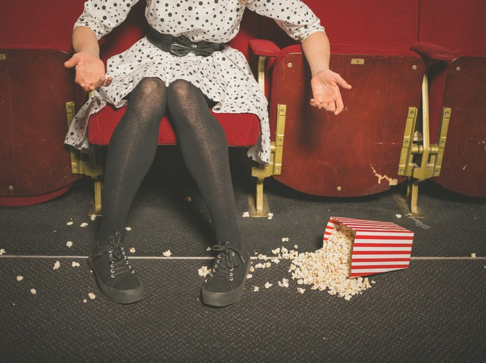 a woman sitting in a movie theater gestures toward a spilled popcorn container.