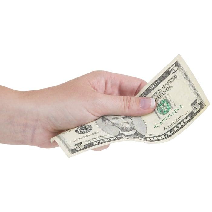 A hand holding a five dollar bill.