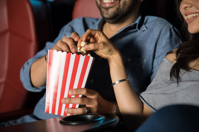 A couple shares popcorn in a movie theater.