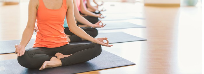 Women sit in the lotus pose on yoga mats in a yoga studio.