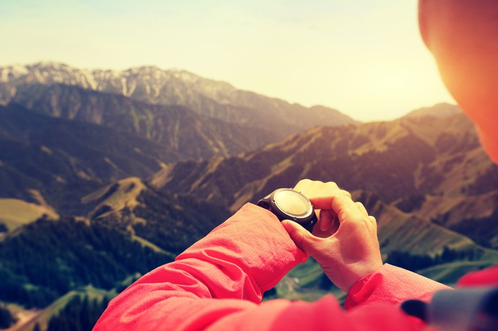 A hiker in the mountains looking at a GPS watch.