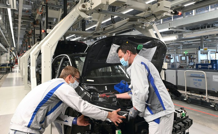 Two workers wearing masks tend to a partially-assembled VW ID.3 hatchback on an assembly line.