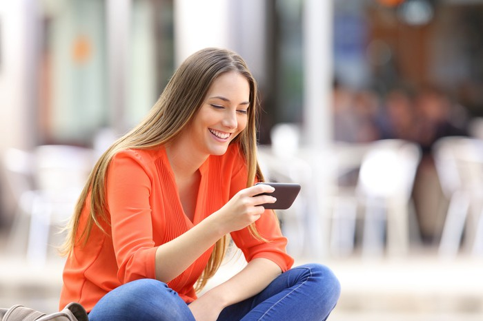 A young woman smiling at her smartphone, sitting outside a bistro-style cafeteria.
