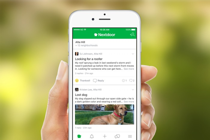 A hand holding the home screen for the Nextdoor app.