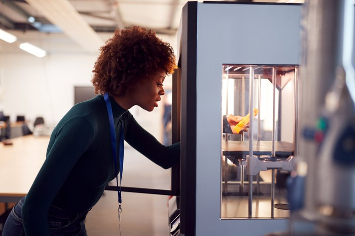 A woman works with a 3D printer.