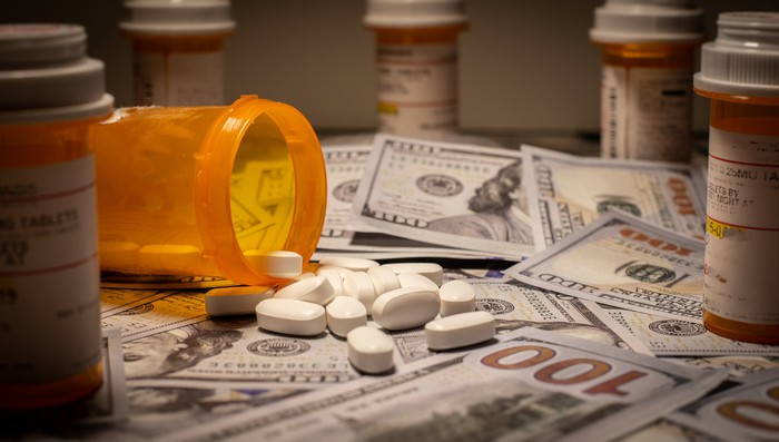 Prescription drugs falling out of a bottle onto cash, with other prescription bottles making a circle around the money.