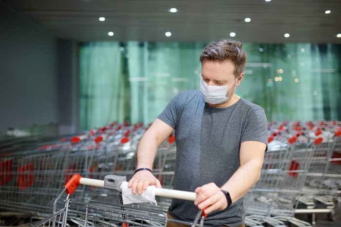 A man in a face mask sanitizing a shopping cart handle.