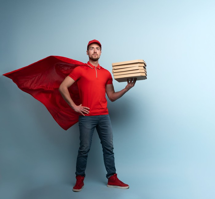 A man wearing a red cape and cap is holding 5 pizzas in his left hand.