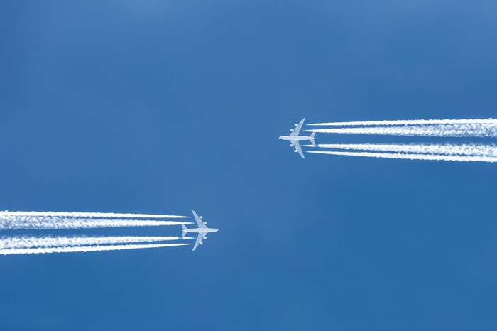 Two airplanes flying toward each other from opposite directions.