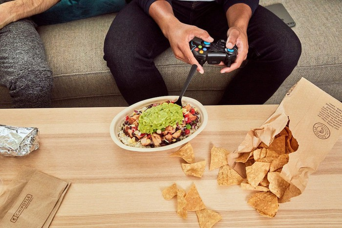 Man with a remote control in his hand sitting in front of a plate of food from Chipotle.