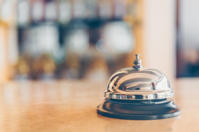 A bell sitting on a hotel front desk with the lobby in the background