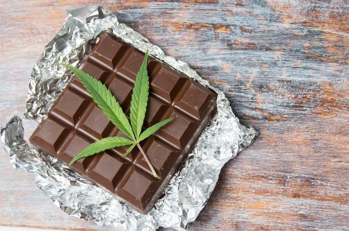 A bar of chocolate with a marijuana leaf on top.