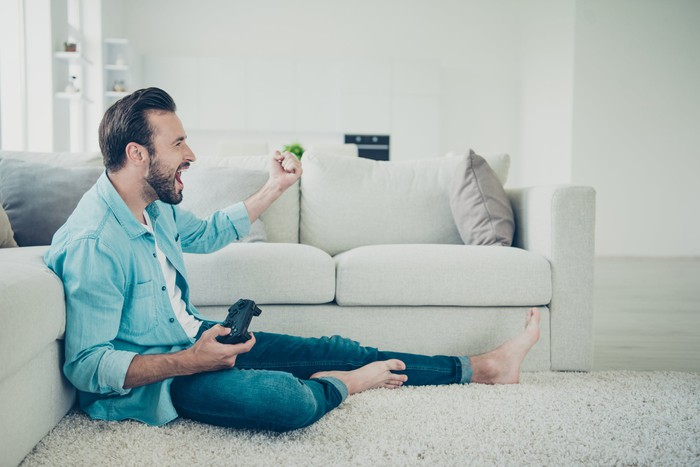 A man having a good time playing a video game while sitting on the floor.