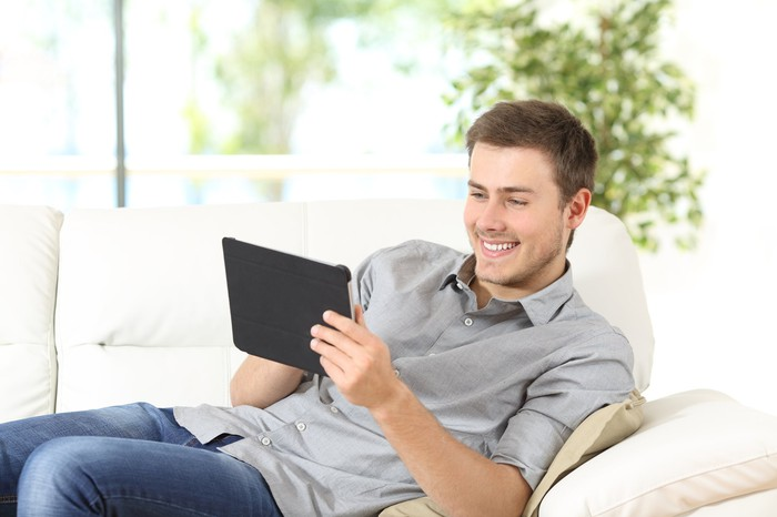 A young man leaning sideways on a soft couch, smiling at his wireless tablet computer.