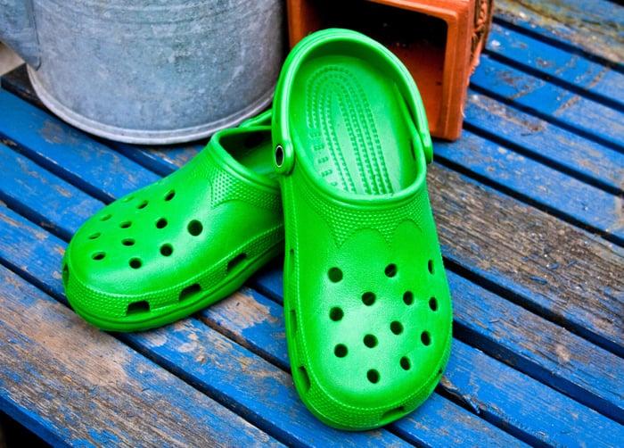 A pair of bright green Crocs on blue slats of wood