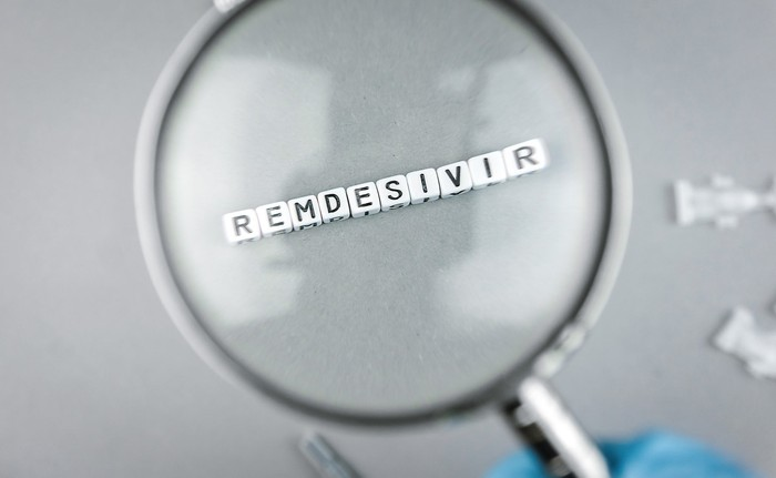 A magnifying glass over cubes spelling out Remdesivir