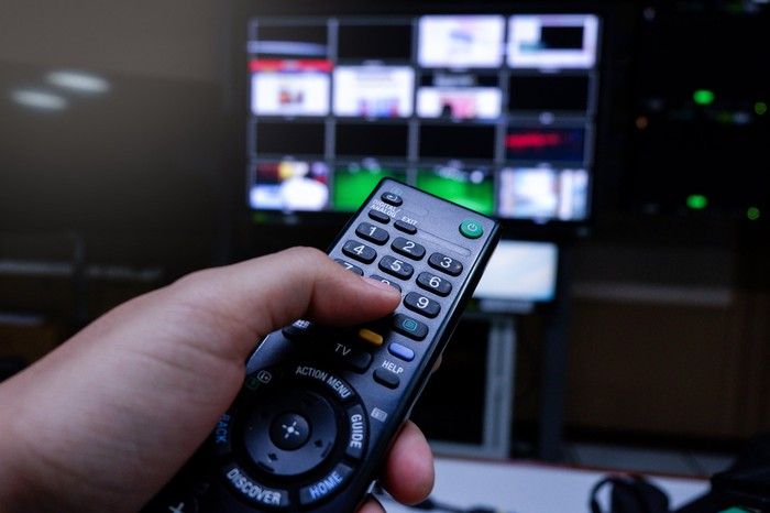 A hand holds a TV remote to change channels on a TV in the background of a dark room