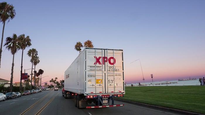 An XPO truck on a coastal road.
