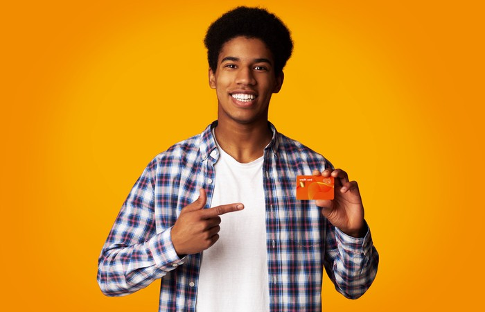 A young man points to a credit card in his other hand.