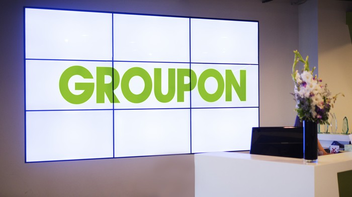A reception desk at a Groupon office with the company's moniker spelled out on nine monitors mounted on the wall.